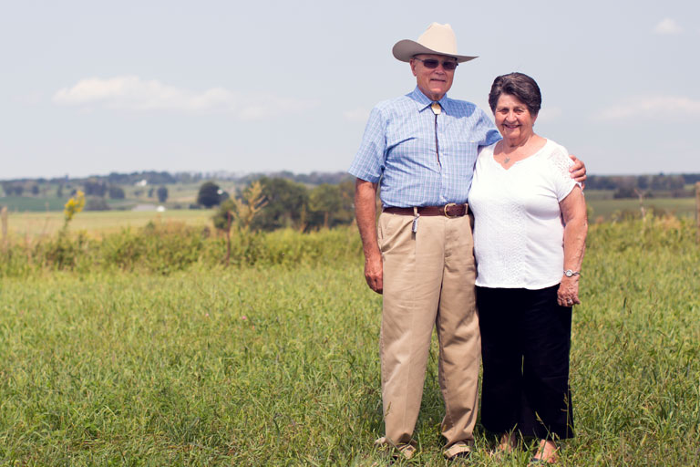 George Sorrells and his wife standing in a field.